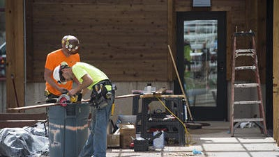 A construction crew works on the finishing touches to an expanded tasting room that opened last week at New Belgium Brewing Co.  A slowdown in building permits has led to a slump in use tax revenue.