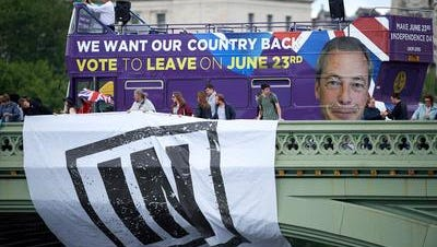 Campaigners to remain in the European Union unfurl a banner on Westminster Bridge as a bus bearing a message urging voters to leave the EU drives by Wednesday in London.