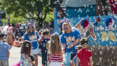 Participants are surrounded by soap bubbles during the 2016 Independence Day Parade in Northville.