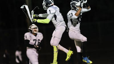 New Brunswick's Kadas Reams, left, celebrates after scoring a touchdown with teammate German Pimentel during a game in East Brunswick on Nov. 4, 2016