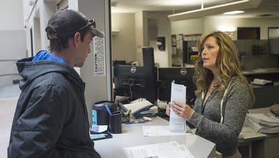 Building and Review Technician Denise Warren assists Spencer Nemnich with some paperwork at the City of Fort Collins Building Department on Wednesday, Nov. 1, 2017.