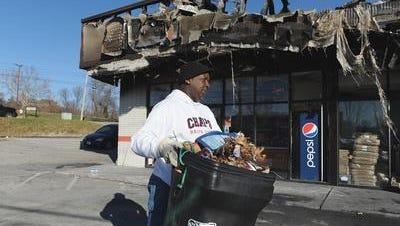 A volunteer helps clean up at a Little Caesars pizza shop that was burned during rioting in Ferguson, Mo.