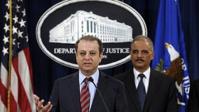 In this March 19, 2014, file photo, Attorney General Eric Holder listens at right as U.S. Attorney for the Second District Preet Bharara talks about the $1.2 billion settlement with Toyota over its disclosure of safety problems during a news conference at the Justice Department in Washington. The Justice Department socked Toyota with a $1.2 billion penalty last week for concealing dangerous defects in some cars. Yet itÂ?s unlikely anyone will go to jail. Prosecutors say they had little choice but to accept that outcome because of constraints with evidence and the challenge of gathering testimony and information from witnesses abroad.