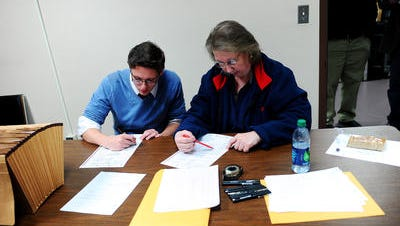 Jesse Fonkert, left, and Paula Johnson, both with the resolution board, work on reading ballots from Minnehaha County early on Wednesday morning, Nov. 5, 2014, after the midterm election at the Minnehaha County Administration building in Sioux Falls, S.D.