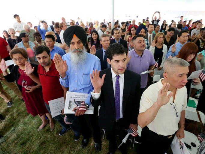 A total of 101 people from numerous countries were sworn in as US citizens during a Naturalization ceremony Thursday, July 3, 2014, morning at the President Benjamin Harrison home. Here Jackson Lee,right, Christian Alvarez,middle, and Sukhpal Singh Kalsi,left in blue, take the pledge. Matt Kryger / The Star