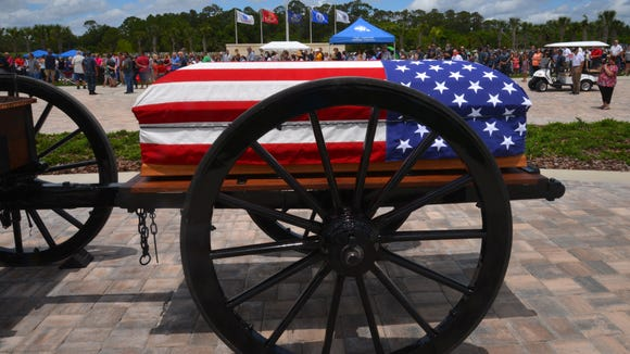 A symbolic flag-draped coffin on a caisson at the Cape