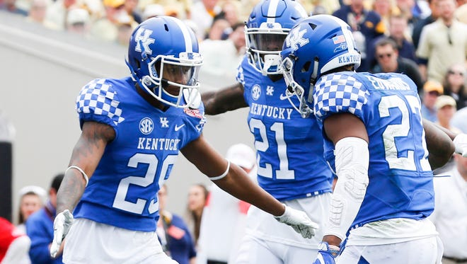 Kentucky's Derrick Baity, left, celebrates with teammates Chris Westry and Mike Edwards after Baity broke up a pass play.December 31, 2016