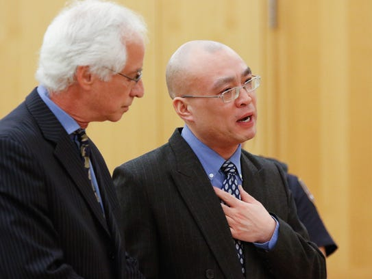 Hengjun Chao, right, reads a statement to the court