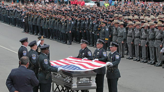 With thousands of law enforcement saluting, the US flag is folded over the coffin of Rochester Police Officer Daryl Pierson during his funeral service at the Blue Cross Arena.