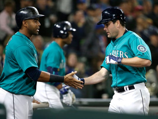 Seattle Mariners' Seth Smith, right, is greeted by teammate Nelson Cruz after Smith hit a solo home run against the Kansas City Royals during the sixth inning of a baseball game, Friday, April 29, 2016, in Seattle. (AP Photo/Ted S. Warren)