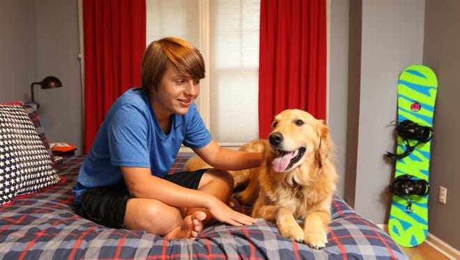 Jack DeSavino poses with his autism service dog, Nardi, in their River Edge home. Tuesday, June 13, 2017