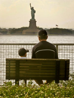 Josef Morvai and his son Daniel Morvai, 4, view the Statue of Liberty on June 20, 2006, from a park bench in Red Hook Garden Pier in Brooklyn, N.Y. New York reached a deal to reopen the statue Friday. It has been closed by a government shutdown.