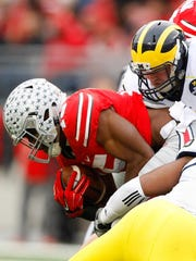 Ohio State's Ezekiel Elliott is tackled in this season's game against rival Michigan.