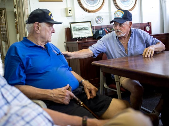 James Hiller, who served on USCGC Storis, reaches over to Ron Kubeck, who served on USCGC Spar, as he recalls circumnavigating the Northwest Passage in 1957 Saturday, July 23, 2016 on the retired USCGC Bramble in Port Huron.