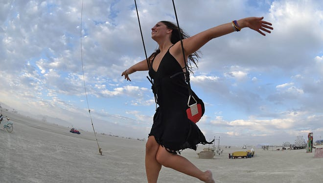 Breanne Gallagher, of San Francisco, soars through the air in a giant swing at Burning Man on August 27, 2017.
