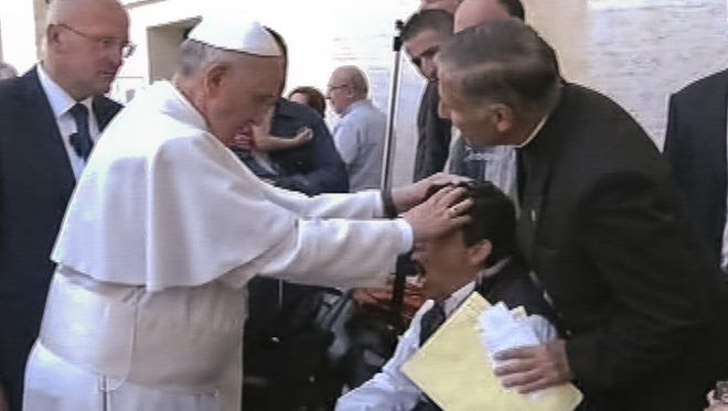 Pope Francis lays his hands on the head of a young man on May 19, 2013, after celebrating Mass in St. Peter's Square