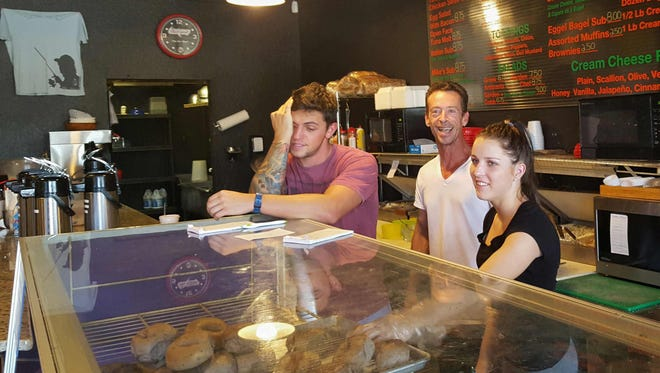 Beachside Bagel World owner John Briody, center, says he disregarded the storm evacuation in order to serve locals.