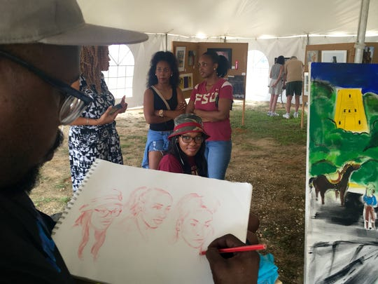 Carter J. Gaston draws a sketch of a mother and her two daughters Saturday at the Celebrating Brownsville Arts and Cultural Festival.