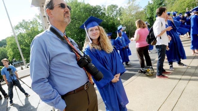 Greg Townsend, principal of the School of Inquiry and Life Sciences at Asheville, stands with SILSA graduating senior, Isabelle Sloan, 18, as students are arranged for a cap and gown photograph at Asheville High School on Thursday. Townsend will be retiring at the end of June.