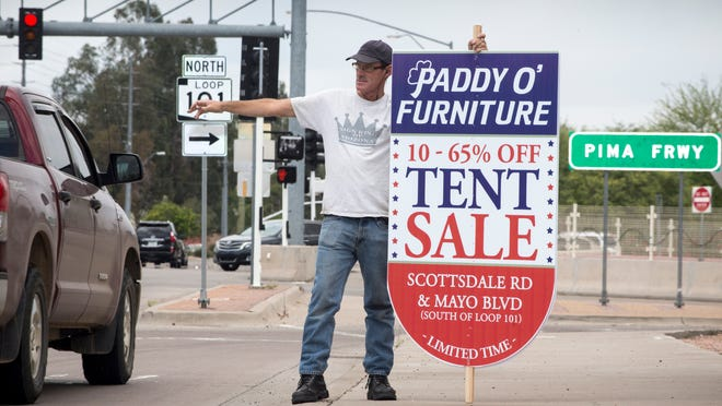 Butch Franklin works the traffic with a â??Paddy Oâ?? Furnitureâ? sign, May 15, 2015, on the northeast corner of the 101 and Shea Blvd., Scottsdale.