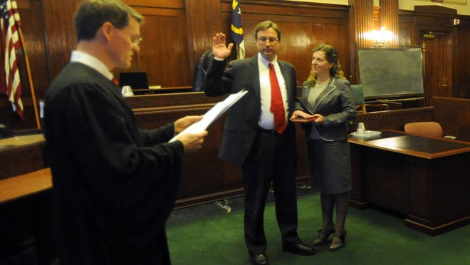 Buncombe County Assistant District Attorney Rodney Hasty with wife Candace listen as Buncombe County Judge Alan Thornburg reads the oath of office during a special ceremony held at the courthouse Thursday Jan. 1, 2015. Hasty died Oct. 12 from a fentanyl and ethanol overdose.