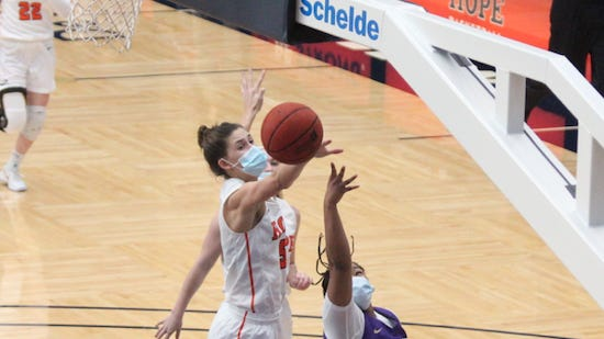 Hope's Olivia Vouskil (left) records one of her nine blocks against Albion College on Saturday, Jan 23 in Holland