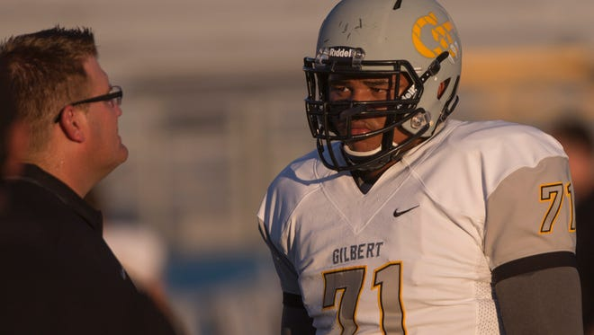 Offensive lineman Steve Miller from Gilbert High School listens to coaches before a game at Mesquite High School on Thursday, August 28, 2014, in Gilbert, Arizona.