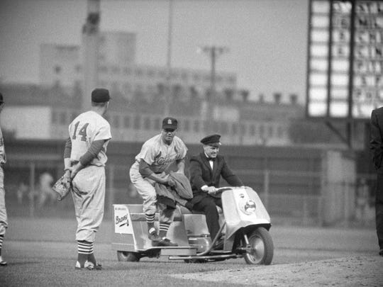 """At Milwaukee's County Stadium on June 23, 1959, St. Louis Cardinals pitcher Hal Jeffcoat arrives at the mound, chauffeured by John """"Freckles"""" Bonneau of Harley-Davidson Co. The trip, which took less than 30 seconds from the bullpen to the pitcher's mound, reportedly was the first time a vehicle was used to bring a pitcher to the mound in the National League. This photo was published in the June 24, 1959, Milwaukee Journal."""