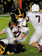 Jowon Briggs (72) of Walnut Hills (on ground) pulls down Turpin's Nathan Hooper for a loss, September 23.