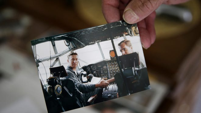 Bill Remter holds a photo taken in 1969 when he was sworn back into the Air Force in a C-130.