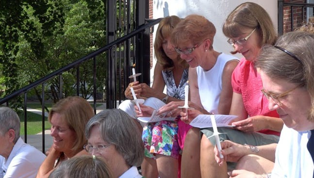 From left, Patty Driver Smith of Isle of Palms, South Carolina, Rachel Moore-Mead of Arnold, Maryland, and Wendy Debold Wyshock of Montoursville, light candles with 19 others who all met freshman year, to honor Lehigh Valley's Patti Little of Bethlehem and Barb Lebo of Phillipsburg, New Jersey.
