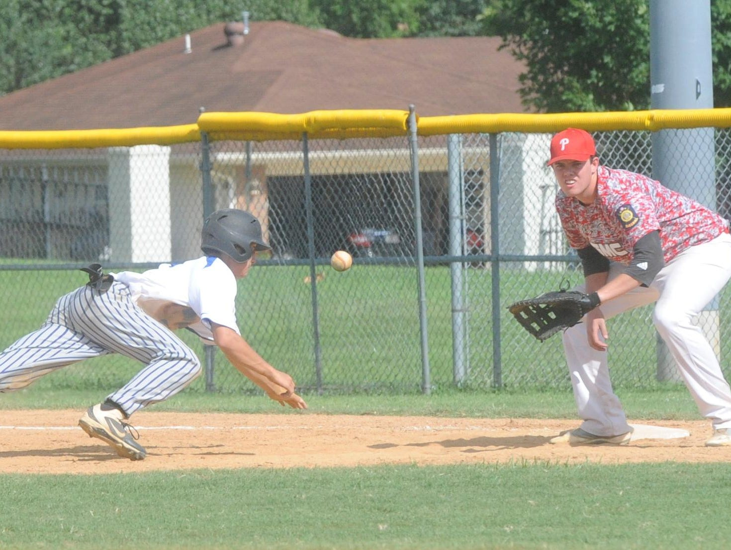 Mountain Home's Luke Kruse, left, dives back into first base as Paragould first baseman Ty Gordon awaits the throw.