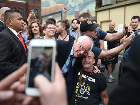 A staffer takes a photo of Bernie Sanders with Chip Becker of York. The Democratic presidential candidate greeted supporters outside the White Rose Bar and Grill in York after he stopped for dinner on April 22, 2016.