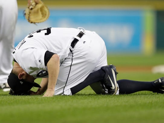 Alex Wilson reacts after being hit by a ball during