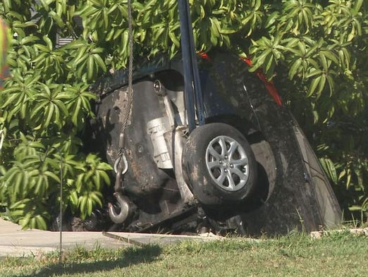 A crane lifted a car out of a sinkhole in Holiday on