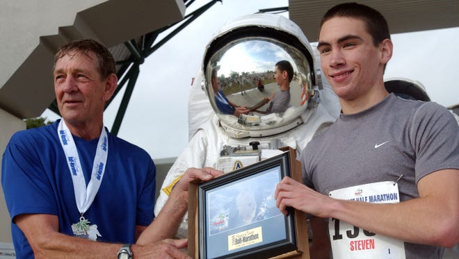Retired NASA astronaut Mike McCulley, left, hands out awards after the 2008 Space Coast Marathon and Half Marathon. McCulley did so after completing the half marathon.