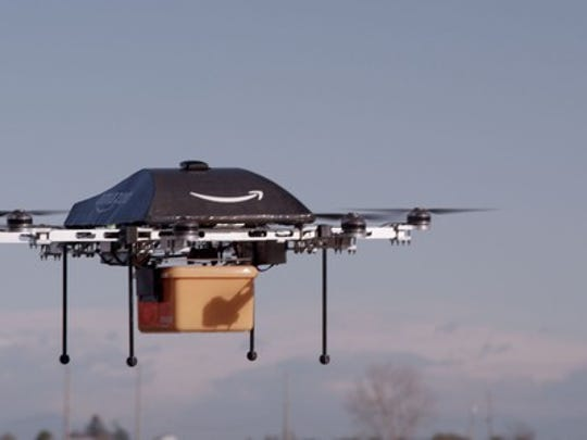 An Amazon-branded drone mid-flight holding a package in a yellow container.