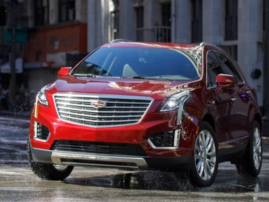 A red Cadillac XT5, a midsize crossover SUV, on a city street.