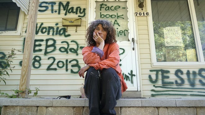 Gina Fournier sits on the porch of her Deering Street home that she spray-painted with graffiti.