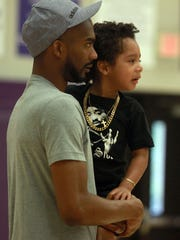 Corey Brewer and son Sebastian (3) watch some drill