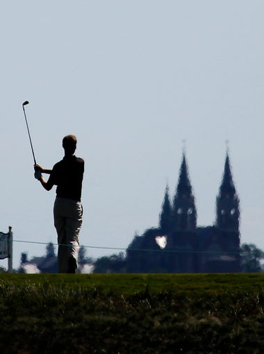 Golfers are silhouetted on the sixth tee with a view of Holy Hill in the background at the 2011 U.S. Amateur at Erin Hills.