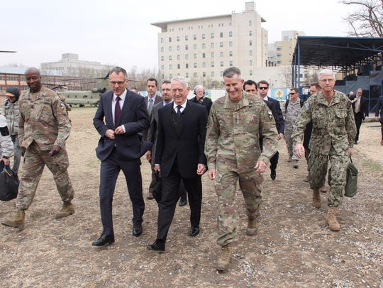 U.S. Defense Secretary Jim Mattis walks with General