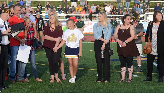 The family of Dominic Ciaramitaro listens as South Lyon VFW's John McMann, at left, reads a dedication to their son and brother who was killed while serving with the Marines in Afghanistan.