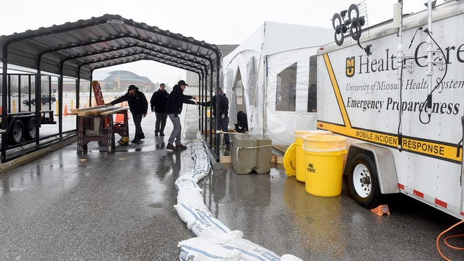 University of Missouri workers prepare a tent to be used as the MU Health Care drive-through COVD-19 testing site in the parking lot east of the Hearnes Center.