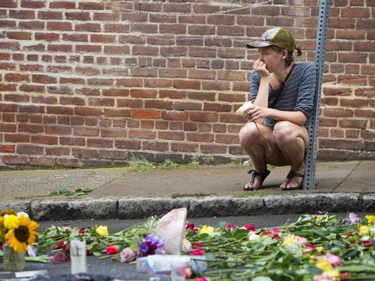 A woman leaves a flower at a memorial at 4th and Water Streets, Tuesday, Aug. 15 2017, in Charlottesville, Va., where Heather Heyer was killed when a car rammed into a group of counterprotesters last weekend. Alex Fields Jr., is charged with second-degree murder and other counts after authorities say he rammed his car into a crowd of counterprotesters Saturday, where a white supremacist rally took place. (AP Photo/Julia Rendleman)