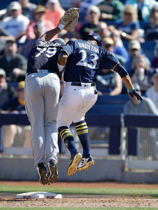 Milwaukee Brewers' Keon Broxton (23) runs into Cleveland Indians first baseman Bobby Bradley after hitting a single to third during the fourth inning of a spring training baseball game, Monday, Feb. 26, 2018, in Maryvale, Ariz. (AP Photo/Carlos Osorio)