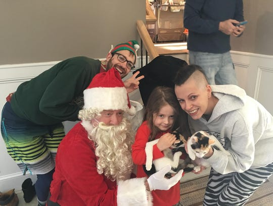 Volunteers from St. Hubert's dressed as Santa Claus and an elf deliver kittens Laverne and Shirley to the Schenk family in Parsippany on Christmas morning, Dec. 25, 2017.