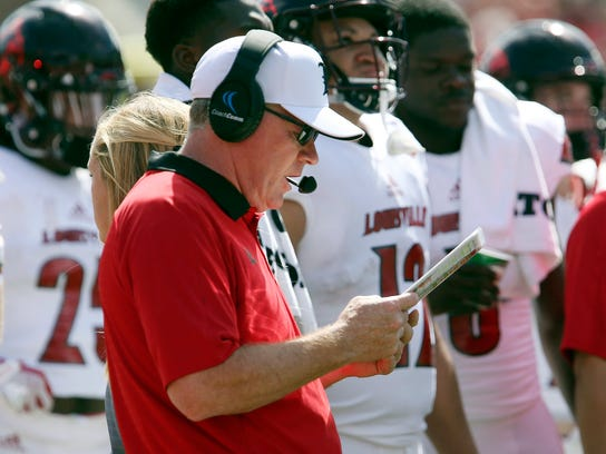 Louisville's head coach Bobby Petrino checks his charts during a timeout in the second quarter of an NCAA college football game with Florida State, Saturday, Oct. 21, 2017, in Tallahassee Fla. Louisville won 31-28. (AP Photo/Steve Cannon)