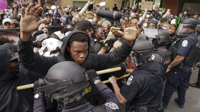 Police and protesters converge during a demonstration on Wednesday in Louisville, Ky. A grand jury has indicted one officer on criminal charges six months after Breonna Taylor was fatally shot by police in Kentucky. The jury presented its decision against fired officer Brett Hankison Wednesday to a judge in Louisville, where the shooting took place.