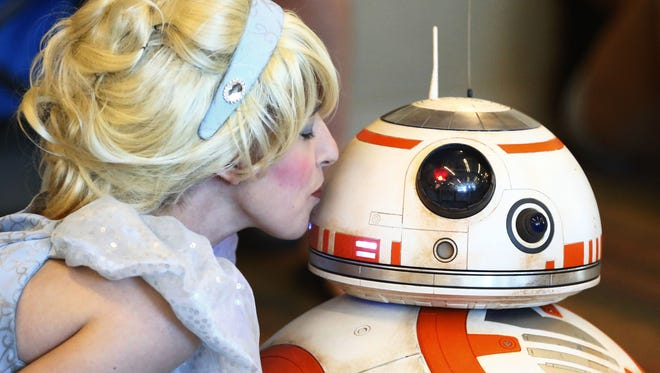 A match made at Disney, Cinderella kisses Star Wars BB-8 droid at Comicon on Saturday, May 27, 2017, at the Phoenix Convention Center.